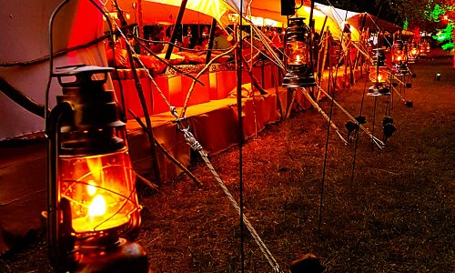 Uplighting & Hurricane Lamps combine to create an inviting entrance to a Stretch Tent